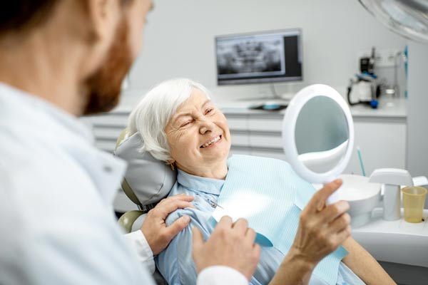 Elderly woman enjoying her new implant anchored dentures at Rogue Valley Dental Center in Medford, OR